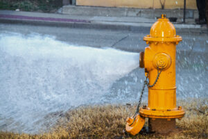 Yellow Fire Hydrant Wide Open Gushing Water Onto The Street With Slightly Grainy Effect Where Water Is Falling Back Down Over The Pavement